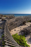 Ancient wooden fence on the background of the sea, the beach. Stock Photos