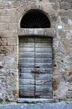 Ancient wooden front door. In a crumbling building, brown, aged, antique, antiquities, arch, architecture, city, doorway, entrance, europe, european, gate stock photo