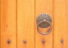 Ancient wooden gate with a door knocker ring. Ancient wooden gate with a rusty door knocker ring close-up stock photography