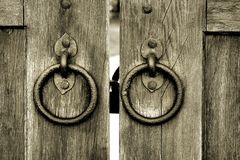 Ancient wooden gate with door knocker rings Royalty Free Stock Photography