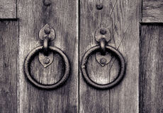 Ancient wooden gate with door knocker rings Stock Image