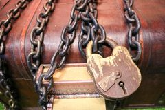 wooden, old, old brown chest locked to a large lock tied with thick, strong metal chains. Stock Images