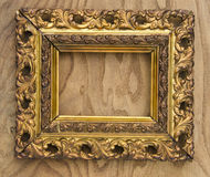 Ancient wooden ornate picture frame on wooden background. Ancient wooden ornate art picture frame on wooden background Stock Image