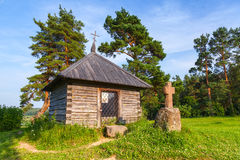 Ancient wooden Orthodox chapel and a stone cross Royalty Free Stock Photos
