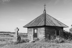 Ancient wooden Orthodox chapel and a stone cross Stock Images