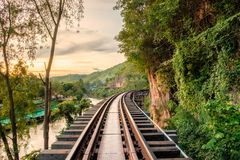 Ancient wooden railway historic of world war II at sunset. Tham Krasae Cave, Kanchanaburi Stock Photos