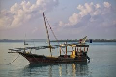 Ancient wooden sailboat on the water surface. Ancient wooden sailing boat on the ocean surface at the morning on the background of clody sky. Coast of Zanzibar stock images