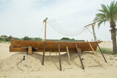 Ancient wooden small ship on the sand in the desert Stock Images