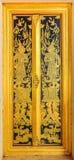 Ancient wooden Thai temple door Stock Photo