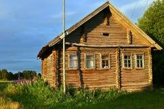Ancient wooden timbered peasant farm hut illuminated sunsets sun Royalty Free Stock Photo