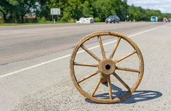 Ancient wooden wheel on a roadside Stock Photo