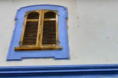Ancient wooden window closed with blue frame on withe wall. Ancient wooden window closed with blue painted frame on withe wall Stock Photos