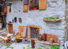 Ancient world. Facade of an old rural house with work tools used in ancient times. Italian Alps Royalty Free Stock Photography