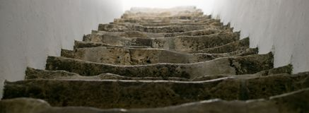 Ancient, worn, stone steps in historic castle, shallow focus. Close up leading to light royalty free stock photography