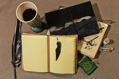 Ancient writer`s worktable. Working place of ancient writer with a cup of wine, old books, quill and other mystic accessories stock photography