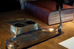 Ancient writing desk. With a feather pen, inkpot and medieval court book Stock Photos