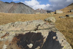 Ancients petroglyph's on the stone. In Tien shan Mountains. NARYN region Royalty Free Stock Photo