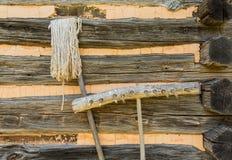 Ancinho e espanador velhos contra a cabana rústica de madeira Imagem de Stock