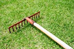 Ancinho que encontra-se na grama no campo de golfe Imagem de Stock Royalty Free