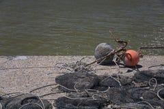 Ancla, flotadores, y redes de pesca en un muelle Fotografía de archivo
