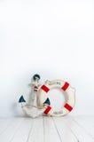 Ancla y boya de vida en un piso de madera blanco Fotografía de archivo libre de regalías