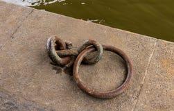 Ancladero oxidado del gancho del hierro del anillo para un barco en una playa de piedra imagen de archivo libre de regalías