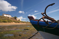 Ancor. A boat´s detail on the foreground with the church and fortress of Cacela Velha on the background (Algarve/Portugal Royalty Free Stock Images