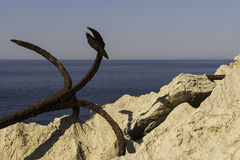 Ancora arrugginita alla costa rocciosa Fotografia Stock Libera da Diritti