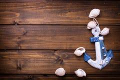 Ancora decorativa e oggetti marini su fondo di legno Fotografia Stock