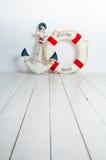 Ancora e salvagente su un pavimento di legno bianco Fotografie Stock