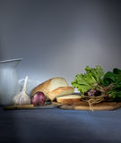Ancora vita 1 brocca, pane, cipolla, aglio, spinaci su una tovaglia blu Spazio per testo Immagini Stock