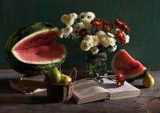 Ancora vita con i crisantemi e l'anguria. Immagini Stock