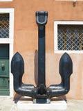 Ancre antique de noir de fer au-dessus de fond rouge de mur Image stock