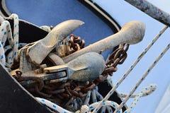 Ancre pliable du petit bateau de puissance placé dans le seau sur l'avant du bateau avec la chaîne et la corde rouillées Photographie stock libre de droits