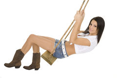 And Beautiful Caucasian Cowgirl Playing On A Wooden Swing Royalty Free Stock Image