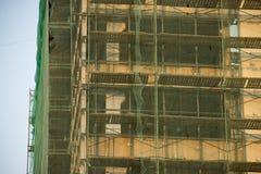 Andaime em uma casa velha para a renovação Fundo bege, verde e azul do ocre Reconstrução das construções e das estruturas Elemen imagem de stock