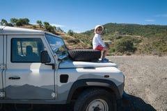 Andalucia rural spain 06/10/2016 Menina que admira a vista ao sentar-se no pneumático de reposição dianteiro em uma capa da capot fotos de stock