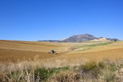Andalucian arable farmland and mountauins. A tractor plowing hillside fields with a farm and mountain scenery under a clear blue sky in andalucia spain Royalty Free Stock Image