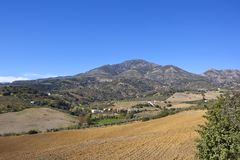 Scenic mountains and countryside of Andalusia. Andalucian farmland with buildings and mountains under a clear blue sky in spain Royalty Free Stock Images