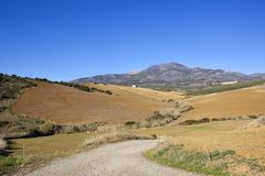 Andalucian farmland landscape with mountains. Andalucian farmland with plowed undulating fields and mountain scenery under a clear blue sky Stock Image