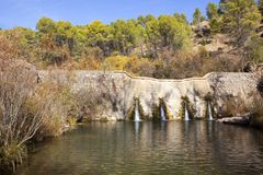 Andalucian landscape with mountain woodlands and river dam. Colorful woodland with a rippled pool and stone dam wall in Andalucia in southern Spain royalty free stock photo