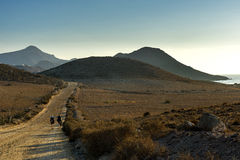 Andalusian countryside. 2 girls with backpack running through the picturesque landscape of Cabo de Gata royalty free stock photo
