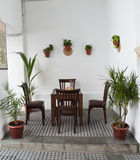Andalusian patio. With tables and four chairs  wood ,and several pots of plants in the wall Stock Image