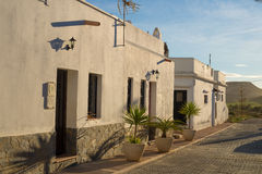 Andalusian village. Traditional Andalusian cobblestone street with sunlit whitewashed facades Royalty Free Stock Photography