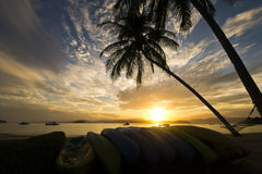 Andaman sea view. Andaman sea view with the sunrise. There is silhouette of Kayaks stacked on the beach, under the coconut trees with cradle as the foreground Royalty Free Stock Photo