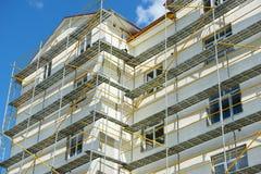 Andamio cerca de una casa bajo construcción para los trabajos externos del yeso, alta construcción de viviendas en ciudad, pared  Foto de archivo