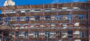 Andamio cerca de una casa bajo construcción para los trabajos externos del yeso, alta construcción de viviendas en ciudad, pared  Imagen de archivo