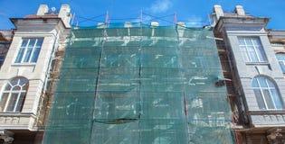Andamio cerca de una casa bajo construcción para los trabajos externos del yeso, alta construcción de viviendas en ciudad, pared  Fotos de archivo libres de regalías