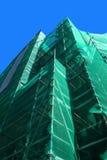 Andamio con la red de seguridad verde Imágenes de archivo libres de regalías