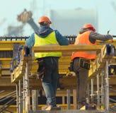 Andamio del metal de la estructura de dos trabajadores en emplazamiento de la obra Imagenes de archivo